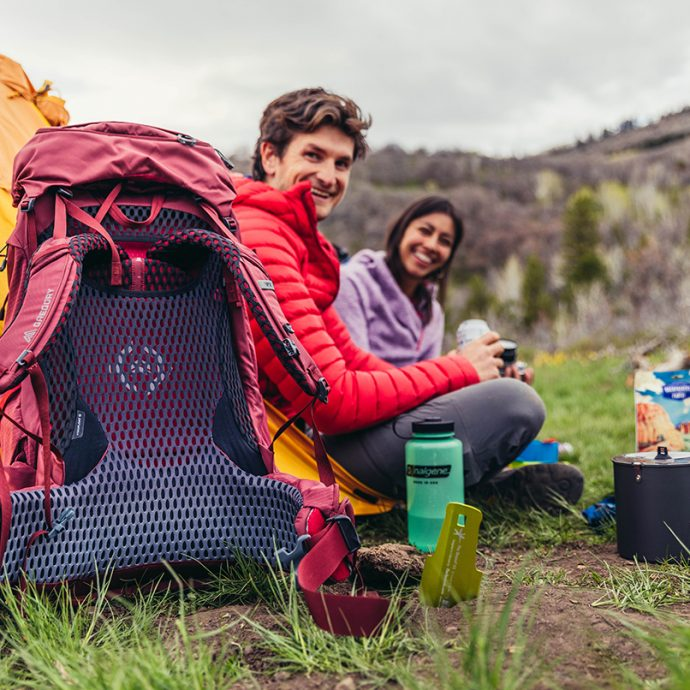 two people camping with backpacks